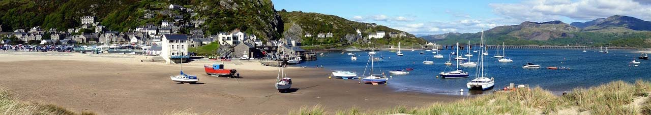 Barmouth harbour with boats on the sand in Wales in Gwynedd